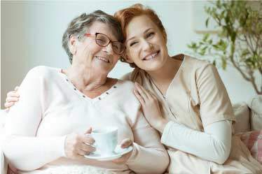 Nurse hugging grandma smiling in a senior care setting