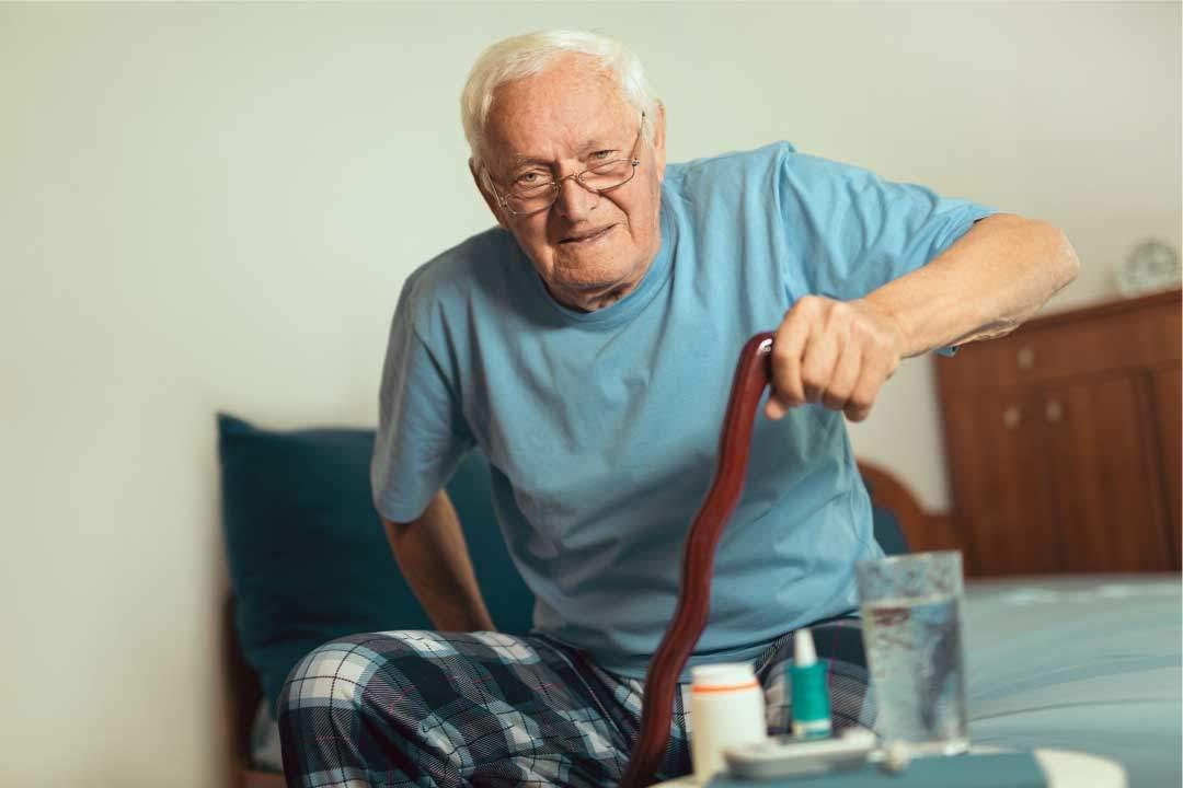 elderly man with cane sitting down