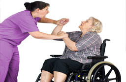 Home care nurse struggling with patient in wheelchair